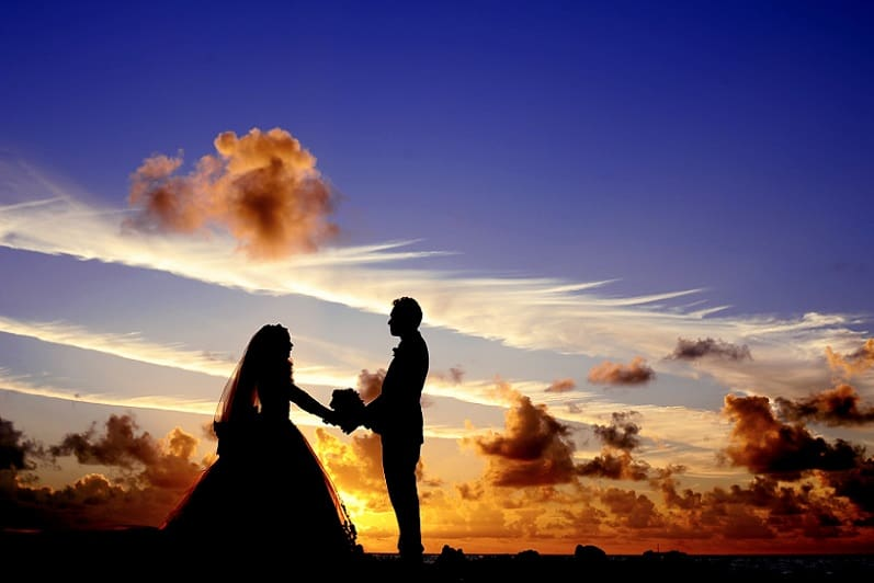 Bruidspaar op het strand, ondergaande zon