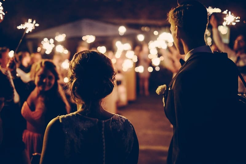 Bruidspaar verlaat de bruiloft 's nachts, bruiloftsgasten zwaaien bruidspaar uit