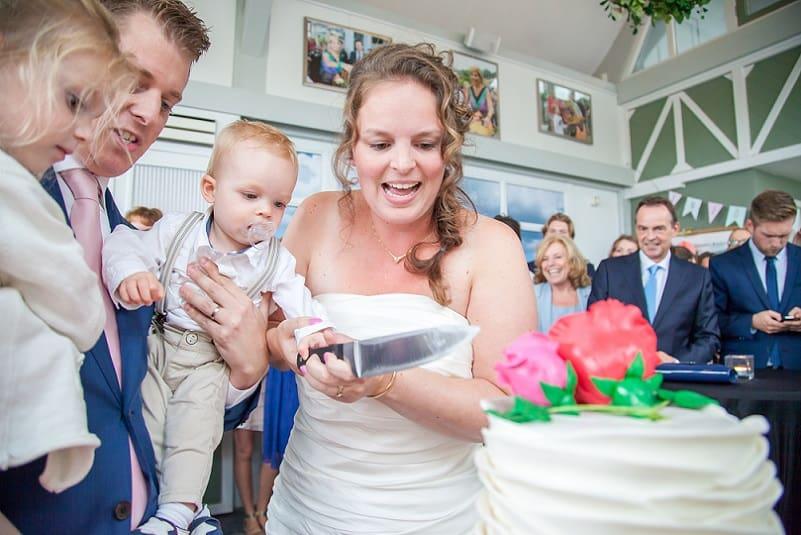 Trouwfotograaf Zoetermeer- Marijke Toorop, bruidspaar snijdt bruidstaart samen aan met kinderen