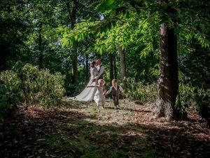 Trouwreportage Goes, bruidspaar met bruidsmeisje en bruidsjonker in bos, Dick